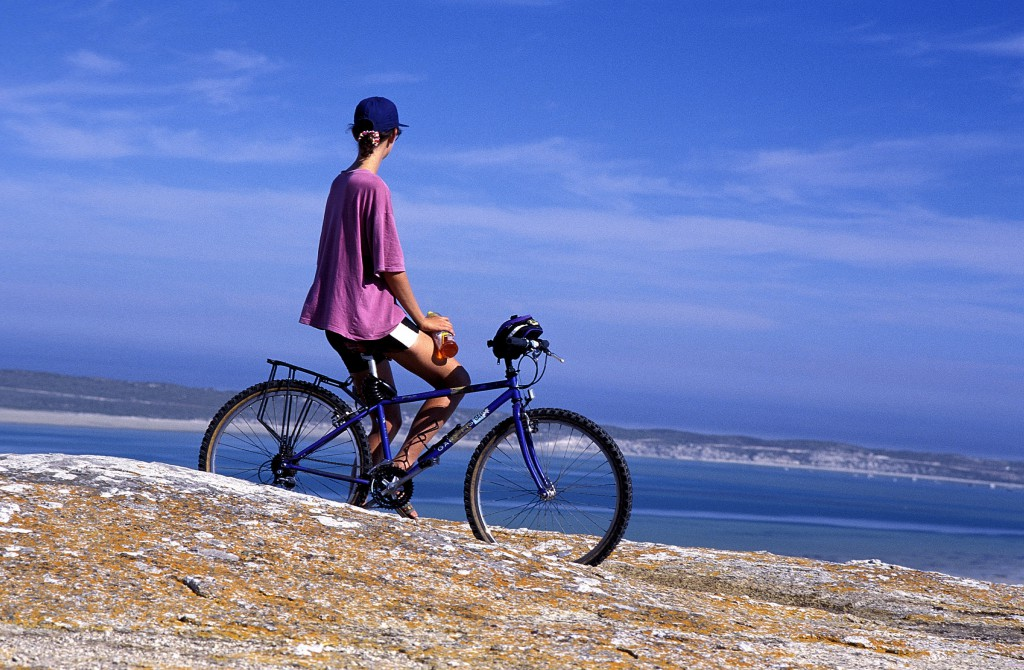 DISTERN00047 People, Leisure, Sport, Cycling. Woman in purple, pink T-shirt and baseball cap on bicycle, resting, looking out over Langebaan Lagoon, ocean, sea. Granite rocks with lichen. ©Jennifer Stern/iAfrika Photos